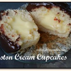 picture of 1 boston cream cupcake split in half on a glass plate