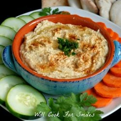 view from above of home made hummus in a blue and orange bowl on a platter with sliced cucumberand carrots and pita break in background to the right