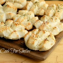 Rosemary parmesan dinner rolls on a wood cutting board on wood table viewed from front