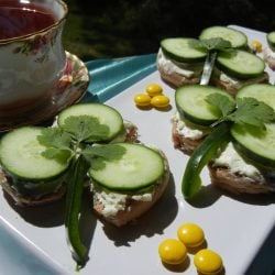 3 cucumber tea shamrock sandwiches on a white plate with a blue table cloth below and a cup of tea in a decorative tea mug to the left.