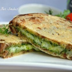 pesto grilled cheese cut in 2 on white plate
