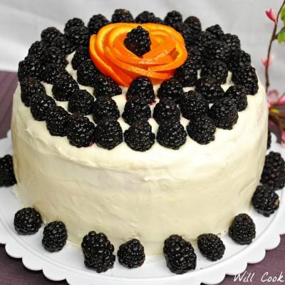 whole blackberry daiquiry cake sitting on a table covered in a purple cloth and decortive branches in the background to the right.