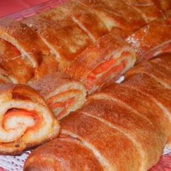 cheesy pepperoni bread rolls on a white cloth on red table viewed from above