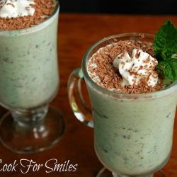 2 decorative dessert mugs filled with adult grasshopper shakes garnished with chocolate shavings, whipped cream and a mint leaf. Both mugs sit on a wooden table.