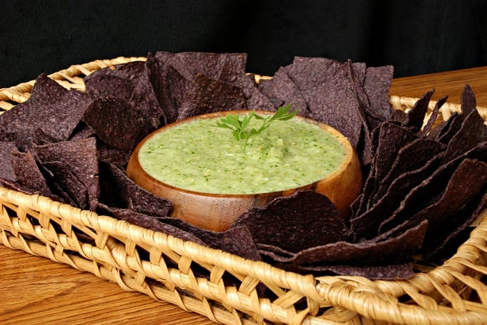 salsa Verde in a wood bowl with purple tortilla chips around it in a brown basket serving tray