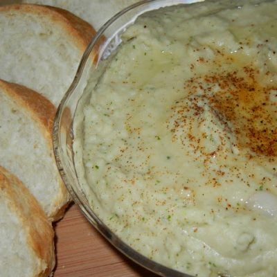 home made hummus in a glass bowl on a wood table with slice bread to the left of bowl