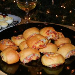appetizer rolls on black plate in front of glass of wine and deviled eggs in background to the left