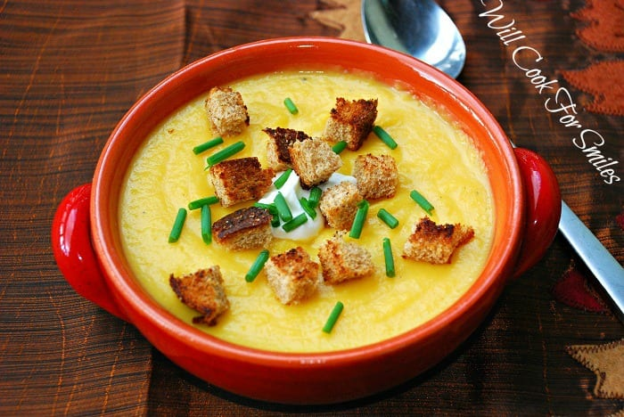 The Best Potato Butternut Squash Soup in a bowl with croutons, sour cream, and chives, on a table with a spoon next to it