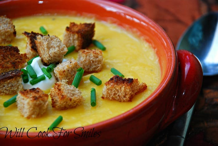 Potato Butternut Squash Soup in a bowl with crotons, sour cream, and chives