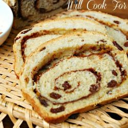2 slices of pumpkin spice swirl bread on a wicker tray with a small white bowl of cinnamon to the left
