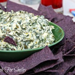 a bed of blue tortilla chips on a platter with a green bowl filled with spinach parmesan dip in the center of chips