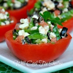 4 stuffed tomato cups on a white rectangular plate on green cloth