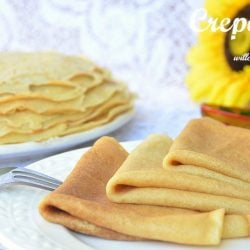 crepes layered and shingled on white plate with fork to the left more crepes on plate in the background