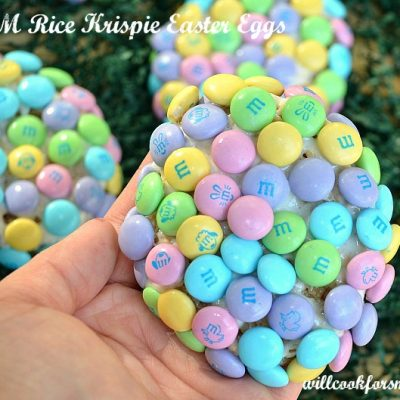 picture of hand holding rice crispy treat egg with m&ms covering it 2 partial crispies in background