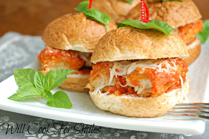 4 chicken parm sliders on white plate with fork in foreground to the right