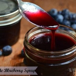 2 mason jars with blueberry syrup one with lid on, 1 spoon in syrup and blueberries on table