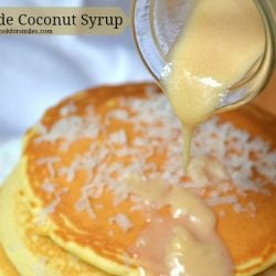 Coconut syrup being poured over stack of pancake that has coconut shaving on top