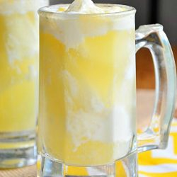 2 clear glass beer mugs filled with skinny pina colada float sitting on white and yellow cloth with burlap cloth to the back left