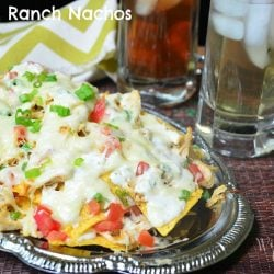 front shot of chicken ranch nachos on silver platter with 2 drinks in glasses in background to the right