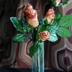 front shot of edible flowers made of bacon in a clear glass vase
