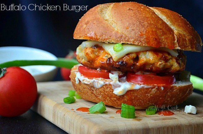 Buffalo Chicken Burger. Juicy chicken burger cooked in buffalo wing sauce and made with ranch dressing, blue cheese crumbles, Mozzarella cheese, and veggies. #burger #sandwich #chicken #buffalo #buffalochicken