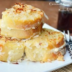 stacked coconut stuffed french toast on white square plate with fork at bottom right and bottle of syrup in background to right