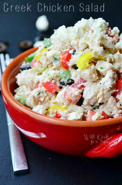 closer view of chicken salad in a red bowl with a fork next to it