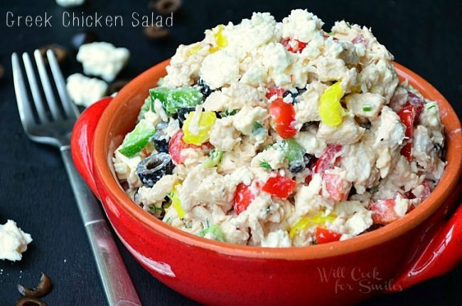 horizontal image of chicken salad in a bowl with a fork next to it and a few feta crumbs
