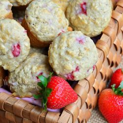 wicker basket filled with mini strawberry oat muffins with knife and butter spread on muffin on table