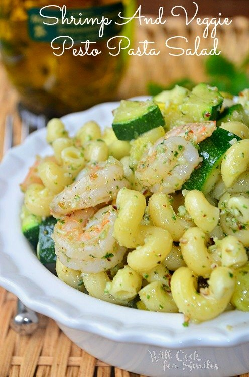 spiral pasta with shrimp and zucchini with herbs in a white bowl
