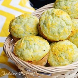 light brown wicker basket filled with zucchini cheddar muffins and 2 muffins below basket