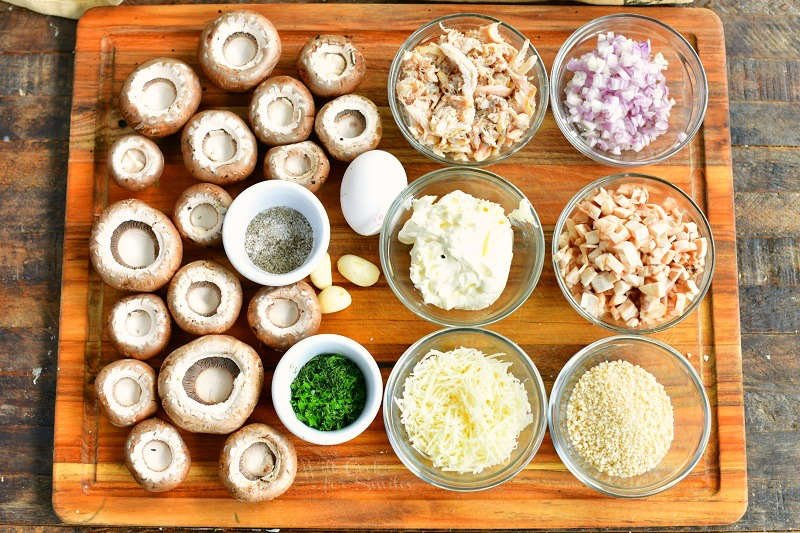 ingredients laid out on the wooden board: mushroom caps, salt and pepper, minced parsley, garlic cloves, crab meat, mayo, parmesan cheese, onion, mushrooms caps, and bread crumbs