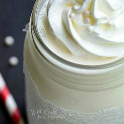 close up picture of mason jar filled with white wedding cake milkshake on a black table with red and white striped straws laying around jar