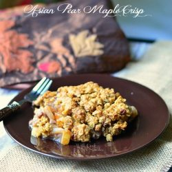 1 portion of Asian Pear crisp on black plate with fork at left all on burlap type placemat