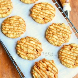several dulce de leche apple caramel oatmeal cookies on cooling rack with wax paper on wood table