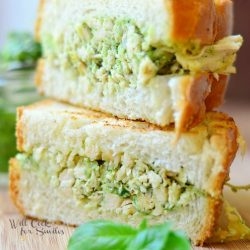 half of sandwich on top of the ther half dilled with pesto chicken salad and leaves of basil next to it