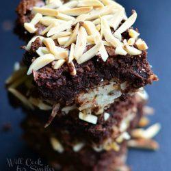 3 almond joy brownies stacked on black table