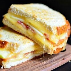 2 halves of apple bacon gouda grilled cheese stacked on each other on wood cutting board