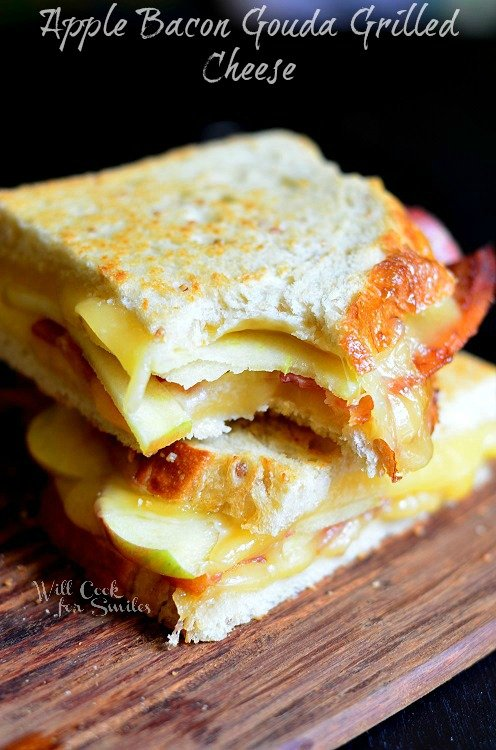 grilled cheese with Apple Bacon Gouda stacked up on a wood cutting board