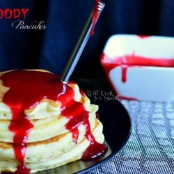 stack of pancakes with red fruit syrup as halloween decor blood to make bloody pancakes on black plate with fork stabbing pancakes and white square dish with more syrup