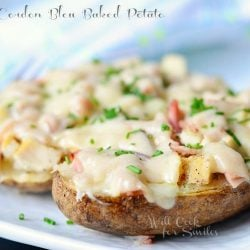 close up picture of 2 chicken cordon bleu baked potatoes on white plate topped with chopped parsley