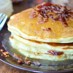 stack of maple bacon pancakes on black plate with fork to the left and syrup jar in background to the left
