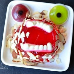 1 monster mash jello creatures on white square plate with candy teeth and eyes