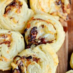 view from above of caramelized onion cheest pinwheels on a brown cutting board