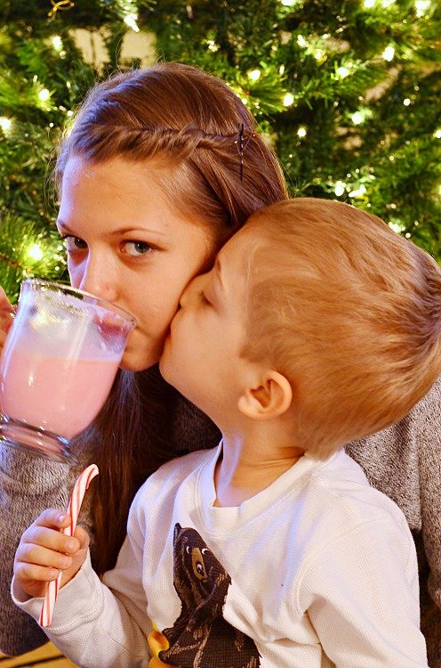 girl drinking the hot chocolate and boy kissing her check while holding candy cane