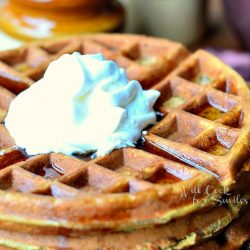 stack of gingerbread waffles with a whipped topping on small plate with fork at the bottom right of plate on a brown placemat. 2 brown and tan jars in background to the left