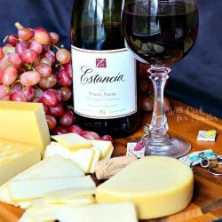 glass of red wine on cutting board with grapes and several different types of cheese and bottle of wine next to cheese