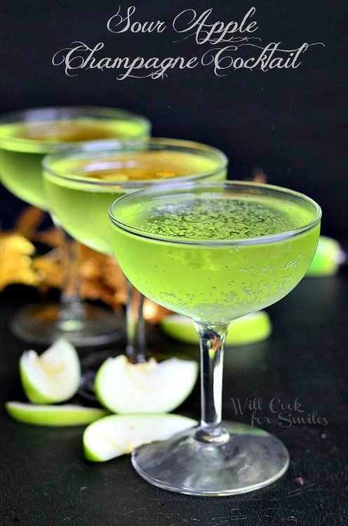 green Sour Apple Champagne Cocktail in a champagne glass on table with sliced green apples around it
