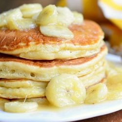 stack of bananas foster pancakes on white plate on wood table with yellow and white cloth in background