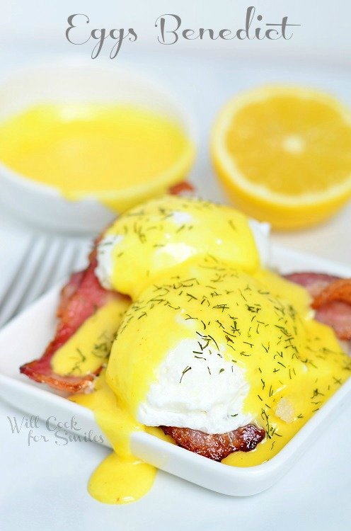 Hollandaise Sauce and Eggs Benedict on a white plate with hollandaise sauce in a small bowl and half a lemon in the background